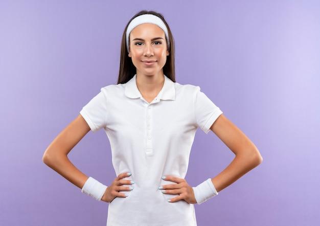 보라색 공간에 고립 된 허리에 손으로 머리띠와 팔찌를 입고 기쁘게 꽤 스포티 한 소녀 무료 사진