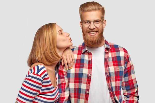ボブの髪型で満足しているきれいな女性は、横に立って、彼女のハンサムなひげを生やしたボーイフレンドの肩に寄りかかっています 無料写真