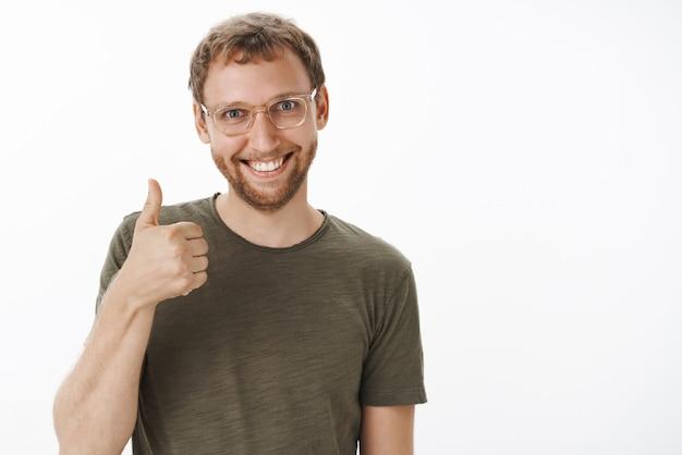 Maschio europeo divertente eccitato soddisfatto e soddisfatto con setola in bicchieri e maglietta casual verde che mostra i pollici in su e sorride con gioia approvando una buona idea Foto Gratuite