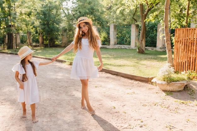 娘を笑顔で見て、手をつないでいるスリムな女性を喜ばせます。茂みのフェンスで庭を裸足で歩いている熱狂的な若い女性の屋外の肖像画。 無料写真
