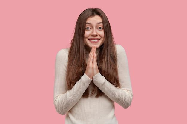 喜んでいる笑顔の女性は、嘆願するような表情をしていて、手のひらを押し付け続け、すべてが良いことを祈っています。長い黒髪で、カジュアルな服を着ています。 無料写真