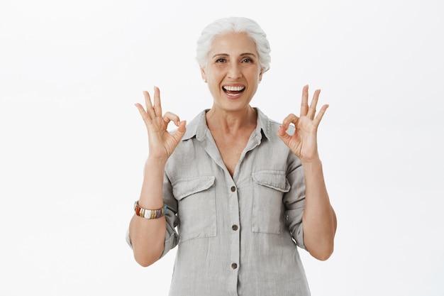 La signora anziana sorridente e soddisfatta che mostra il gesto giusto in approvazione, consiglia la compagnia, come l'idea Foto Gratuite