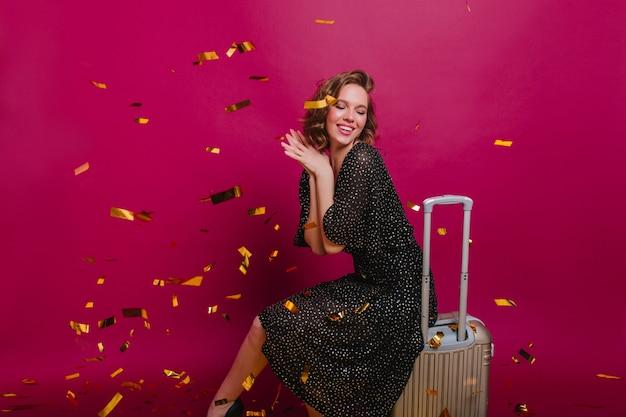 다가오는 여행 전에 보라색 배경에 꿈꾸는 포즈를 취하는 기쁘게 세련된 아가씨 무료 사진