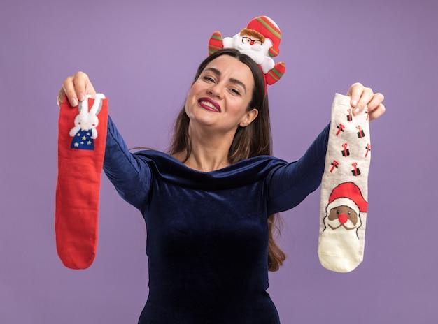 Довольно наклонив голову молодая красивая девушка в синем платье и рождественском обруче для волос держит рождественские носки, изолированные на фиолетовом фоне Бесплатные Фотографии