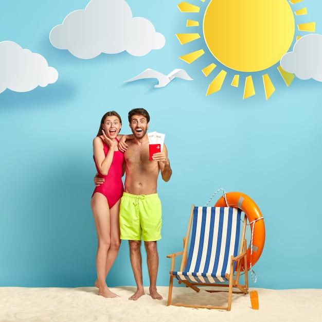 喜んでいる女性と男性は夏の旅行を楽しんで、空飛ぶチケットとパスポートでビーチウェアでポーズをとり、抱きしめて嬉しい表情をしています 無料写真