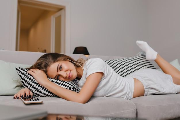 쿠션과 함께 코파에 누워 부드럽게 웃는 양말에 기쁘게 여자 무료 사진