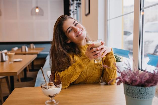 Довольная женщина с темными волосами охлаждает чашкой кофе в уютном кафе зимой. крытый портрет удивительной дамы в вязаном желтом кардигане, отдыхающей в ресторане и наслаждающейся мороженым. Бесплатные Фотографии