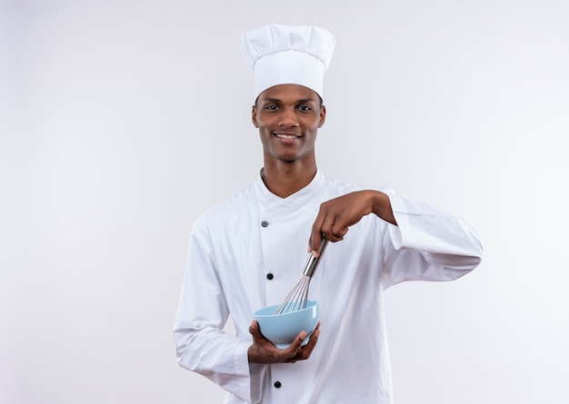 シェフの制服を着た若いアフリカ系アメリカ人の料理人は、コピースペースで孤立した白い背景にボウルと泡立て器を保持します 無料写真