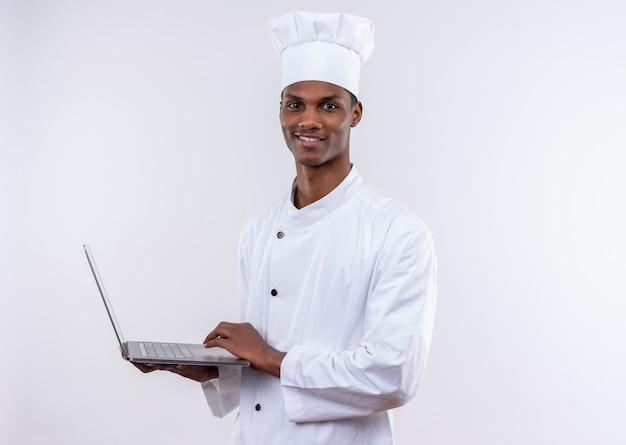 シェフの制服を着た若いアフリカ系アメリカ人の料理人がラップトップを保持し、コピースペースで孤立した白い背景の上のカメラを見て満足 無料写真