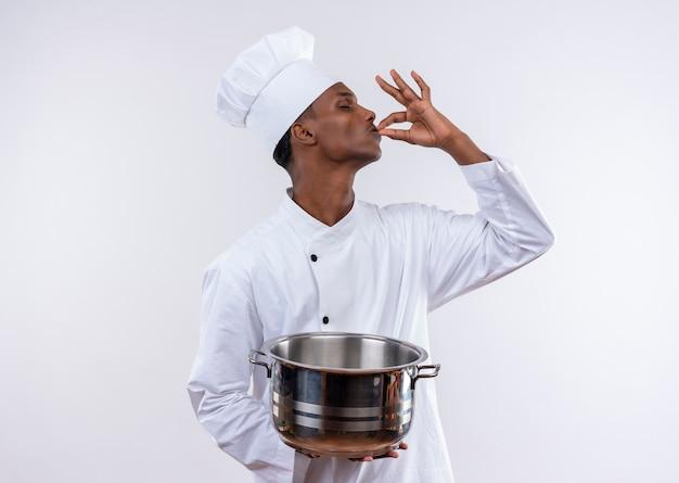 シェフの制服を着た若いアフリカ系アメリカ人の料理人は、コピースペースと孤立した白い背景に手で鍋とおいしいジェスチャーを保持します 無料写真