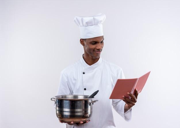シェフの制服を着た若いアフリカ系アメリカ人の料理人が鍋を持って、コピースペースで孤立した白い背景の上のノートを見て喜んで 無料写真