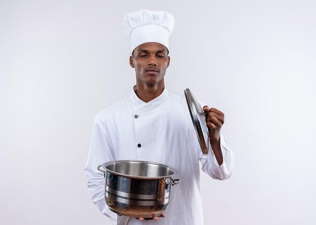 シェフの制服を着た若いアフリカ系アメリカ人の料理人は、コピースペースと孤立した白い背景に目を閉じて鍋を保持します 無料写真