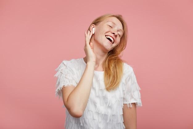 ピンクの背景の上に立っている間、目を閉じて彼女のお気に入りの音楽トラックを楽しんで、前向きに笑って、イヤピースに手を上げて、セクシーな髪の若い魅力的な女性を喜ばせます 無料写真