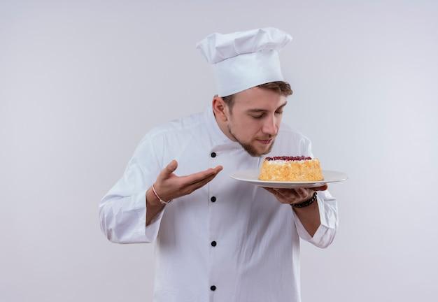 Un felice giovane chef barbuto uomo che indossa l'uniforme bianca del fornello e cappello che tiene un piatto con la torta e l'odore mentre si trova su un muro bianco Foto Gratuite