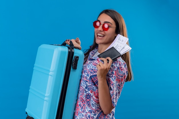 Pleased young beautiful traveler woman wearing red sunglasses holding blue suitcase and tickets smiling cheerfully with happy face over blue wall Free Photo