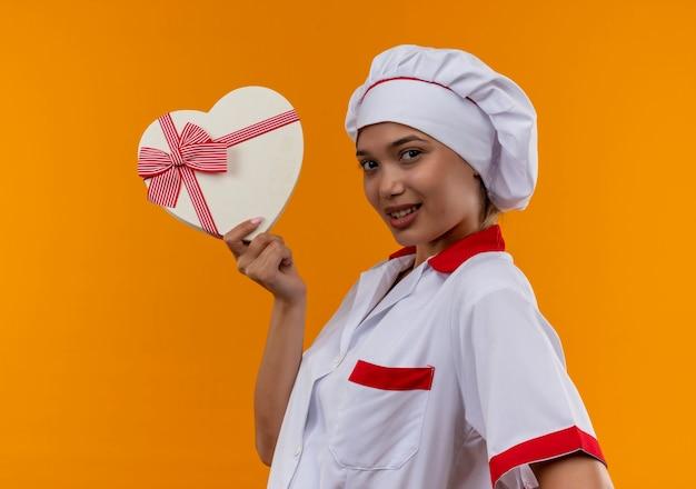 孤立したオレンジ色の壁にハート型ボックスを保持しているシェフの制服を着ている若い料理人の女性を喜ばせる 無料写真
