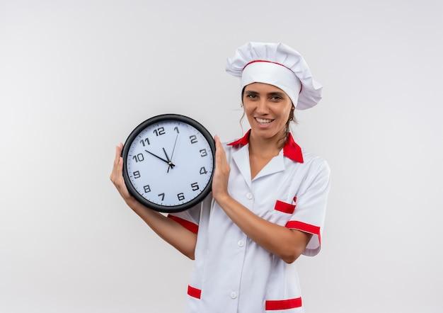 Soddisfatto giovane cuoco femminile che indossa lo chef uniforme tenendo l'orologio da parete con lo spazio della copia Foto Gratuite
