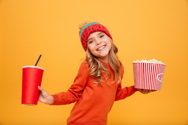 Pleased young girl in sweater and hat holding popcorn and plastic cup while looking at the camera over orange Free Photo