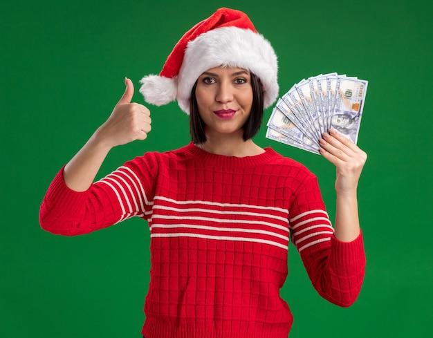 녹색 벽에 고립 엄지 손가락을 보여주는 돈을 들고 산타 모자를 쓰고 기쁘게 어린 소녀 무료 사진