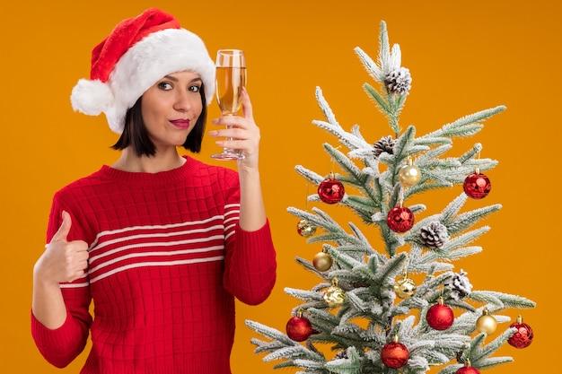 Felice giovane ragazza che indossa il cappello della santa in piedi vicino all'albero di natale decorato tenendo un bicchiere di champagne guardando la telecamera che mostra il pollice in alto isolato su sfondo arancione Foto Gratuite