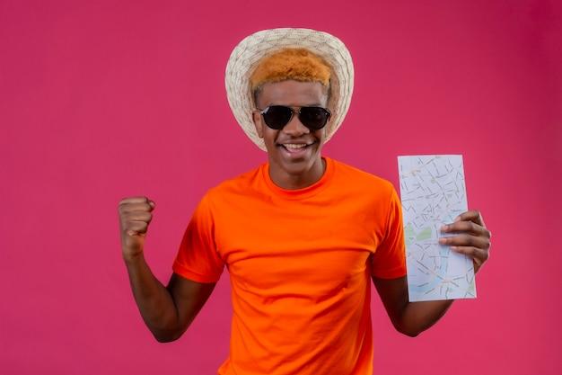Soddisfatto giovane ragazzo bello in cappello estivo che indossa la mappa arancione della holding della maglietta Foto Gratuite