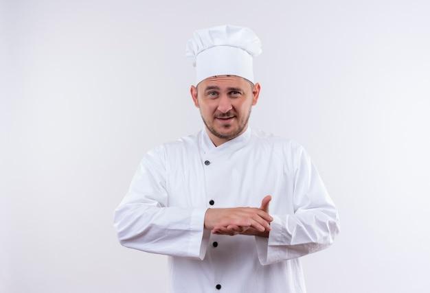 Felice giovane cuoco bello in uniforme da chef tenendo le mani insieme isolato su uno spazio bianco Foto Gratuite
