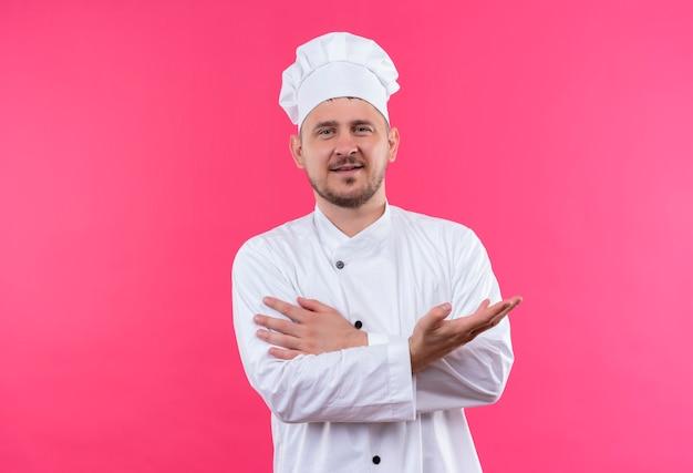 Felice giovane cuoco bello in uniforme da chef che mostra la mano vuota e mettendo la mano sul braccio isolato sullo spazio rosa Foto Gratuite