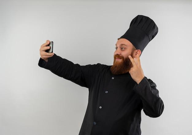 ピースサインをして、白いスペースで隔離されたselfieを取るシェフの制服を着た若いハンサムな料理人を喜ばせる 無料写真
