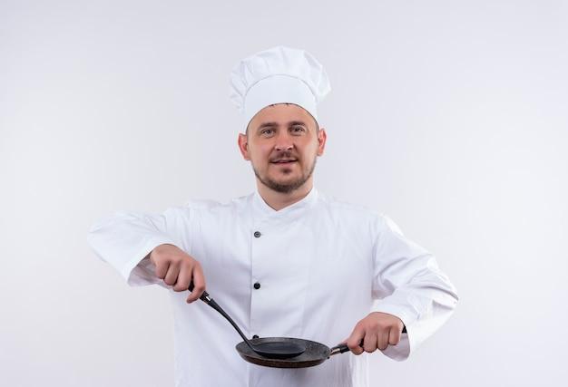 孤立した白いスペースでフライパンとおたまを保持しているシェフの制服を着た若いハンサムな料理人を喜ばせる 無料写真