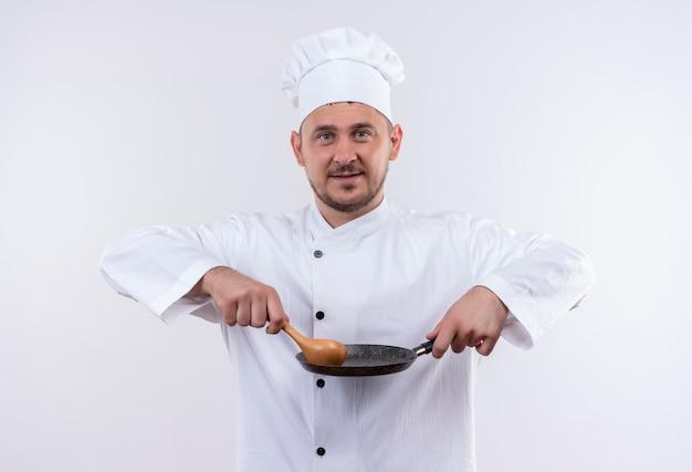 白いスペースで隔離のフライパンとスプーンを保持しているシェフの制服を着た若いハンサムな料理人を喜ばせる 無料写真