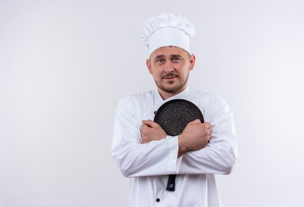 白いスペースで隔離のフライパンを保持しているシェフの制服を着た若いハンサムな料理人を喜ばせる 無料写真