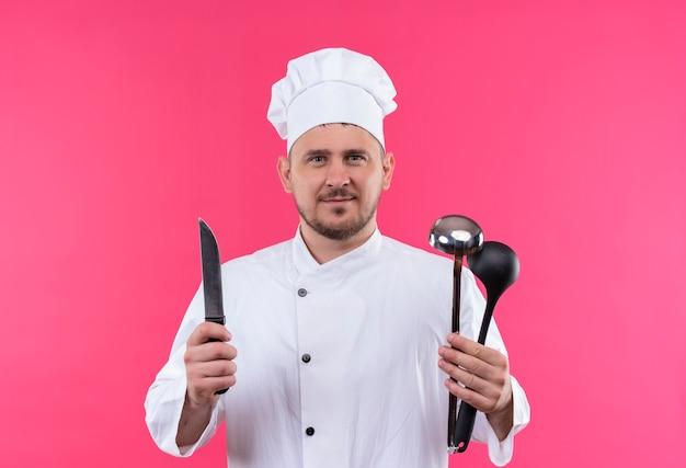 ピンクのスペースで隔離のナイフと鍋を保持しているシェフの制服を着た若いハンサムな料理人を喜ばせる 無料写真