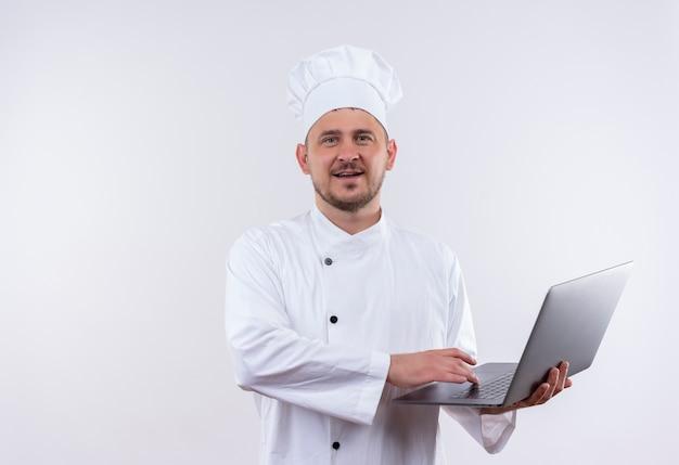 孤立した白いスペースにラップトップを保持しているシェフの制服を着た若いハンサムな料理人を喜ばせる 無料写真