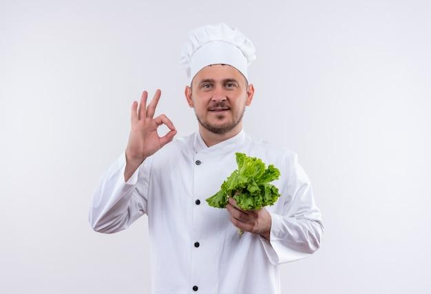 レタスを保持し、白いスペースで隔離のokサインをしているシェフの制服を着た若いハンサムな料理人を喜ばせる 無料写真