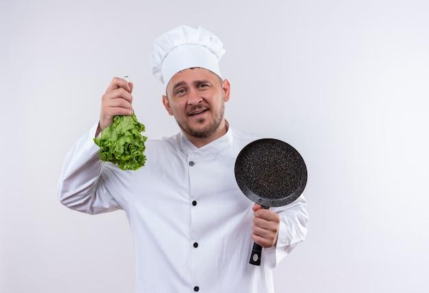 孤立した白いスペースにレタスとフライパンを保持しているシェフの制服を着た若いハンサムな料理人を喜ばせる 無料写真