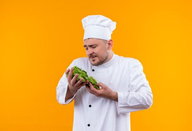 オレンジ色の空間に隔離された目を閉じてレタスを保持しているシェフの制服を着た若いハンサムな料理人を喜ばせる 無料写真
