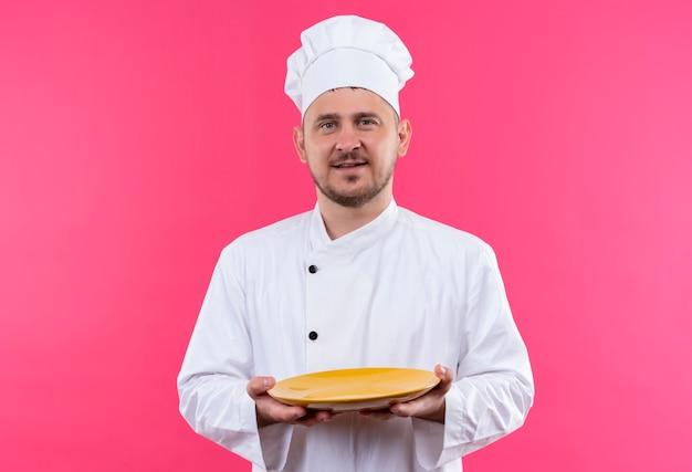 ピンクのスペースで隔離のシェフの制服保持プレートで若いハンサムな料理人を喜ばせる 無料写真