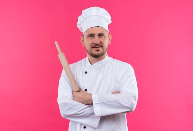 Довольный молодой красивый повар в униформе шеф-повара держит скалку и стоит в закрытой позе, изолированной на розовом пространстве Бесплатные Фотографии