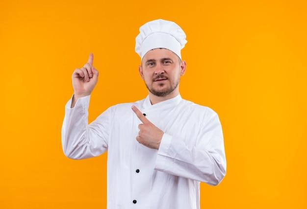オレンジ色のスペースに隔離された上向きのシェフの制服を着た若いハンサムな料理人を喜ばせる 無料写真