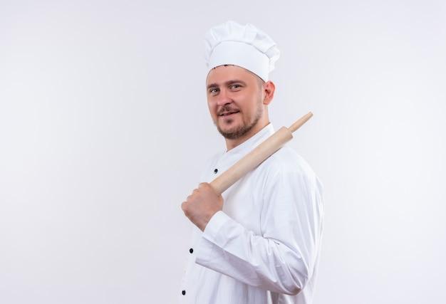 Довольный молодой красивый повар в униформе шеф-повара, стоящий в профиль и держащий скалку, изолированную на белом пространстве Бесплатные Фотографии