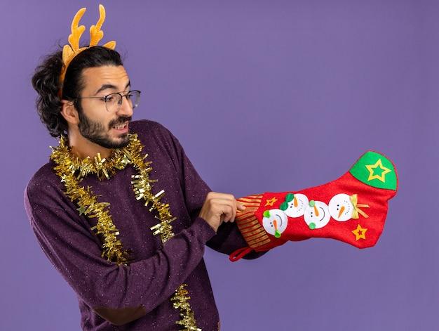 Довольный молодой красивый парень в рождественском обруче для волос с гирляндой на шее держит и кладет руку в рождественские носки, изолированные на синем фоне Бесплатные Фотографии