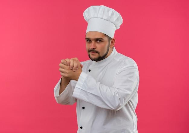 Felice giovane maschio cuoco in uniforme da chef tenendo le mani insieme cercando isolato su uno spazio rosa Foto Gratuite