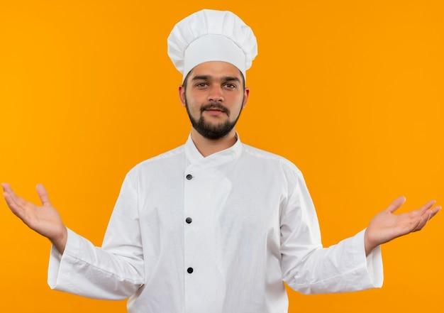 Felice giovane cuoco maschio in uniforme del cuoco unico che mostra le mani vuote e guardando isolato su spazio arancione Foto Gratuite