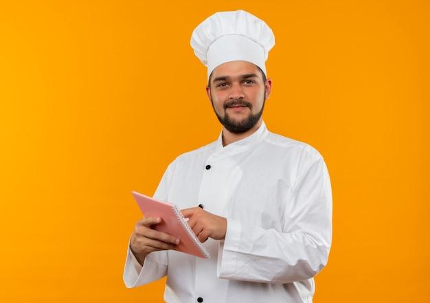 オレンジ色のスペースで孤立しているように見えるメモ帳に指を持って置くシェフの制服を着た若い男性料理人を喜ばせる 無料写真