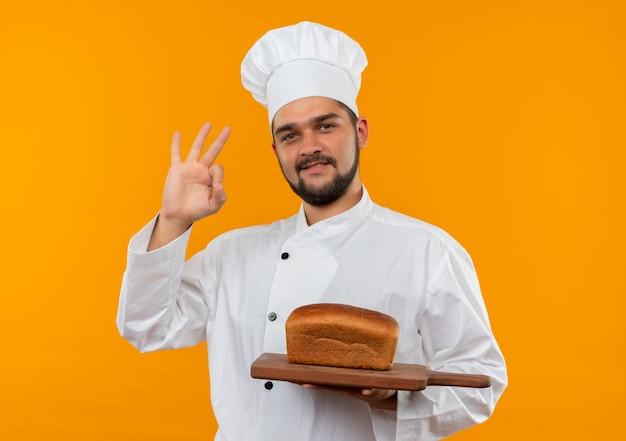 その上にまな板を保持し、オレンジ色のスペースで隔離のokサインをしているシェフの制服を着た若い男性料理人を喜ばせる 無料写真