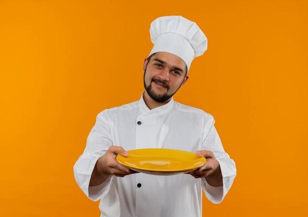 オレンジ色のスペースで隔離の空のプレートを伸ばしてシェフの制服を着た若い男性料理人を喜ばせる 無料写真