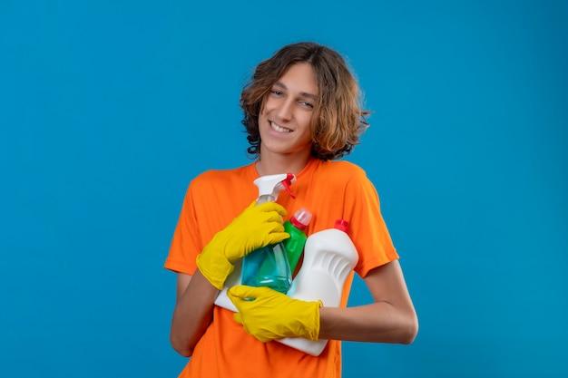 Довольный молодой человек в оранжевой футболке в резиновых перчатках держит инструменты для уборки, глядя в камеру с счастливым лицом, весело улыбаясь, стоя на синем фоне Бесплатные Фотографии