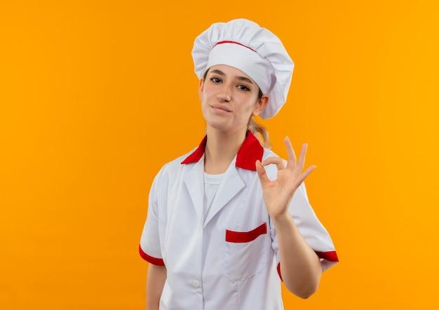 オレンジ色のスペースで隔離されたokサインをしているシェフの制服を着た若いかわいい料理人を喜ばせます 無料写真