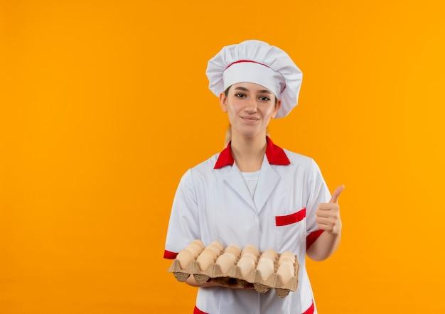 卵のカートンを保持し、オレンジ色のスペースで隔離された親指を見せてシェフの制服を着た若いかわいい料理人を喜ばせる 無料写真