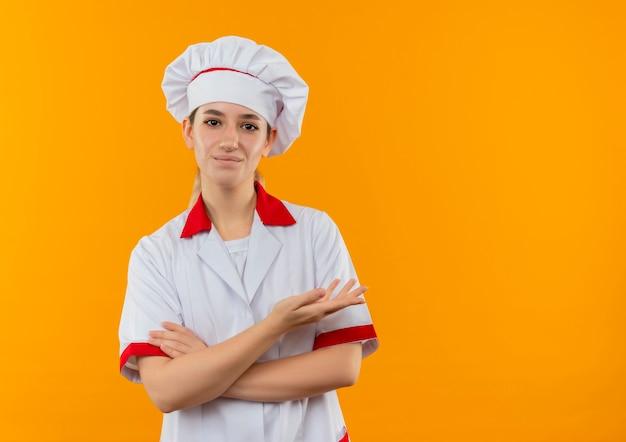 閉じた姿勢で立って、オレンジ色のスペースで隔離された空の手を示すシェフの制服を着た若いかわいい料理人を喜ばせます 無料写真